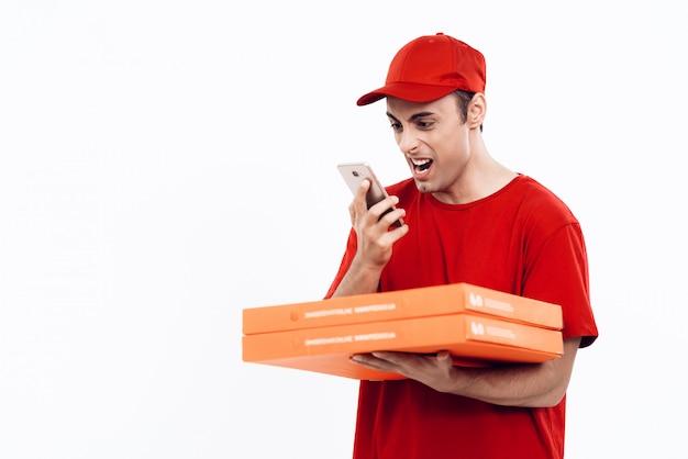 Courier com pizza em uniform shouts into phone. Foto Premium