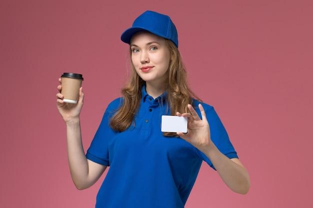 Courier feminino de uniforme azul segurando uma xícara de café marrom com cartão branco na mesa rosa claro. Foto gratuita