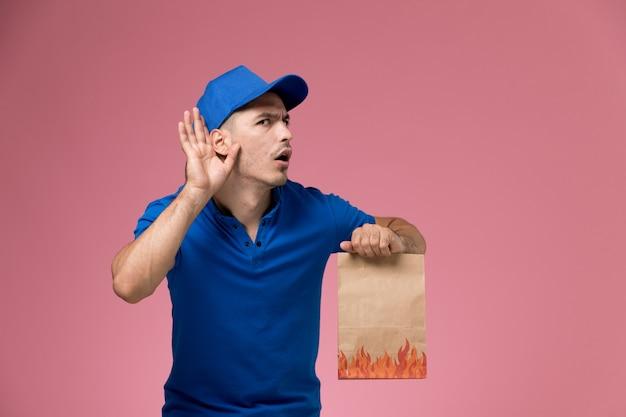 Courier masculino de uniforme azul segurando um pacote de papel e tentando ouvir na parede rosa, entrega de serviço de uniforme de trabalhador Foto gratuita