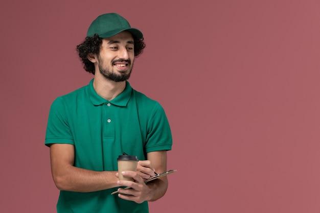 Courier masculino de vista frontal em uniforme verde e capa segurando a xícara de café de entrega com bloco de notas e caneta sorrindo no fundo rosa uniforme serviço de entrega de trabalho de empresa Foto gratuita