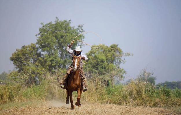 Cowboy com um cavalo e uma arma na mão Foto Premium
