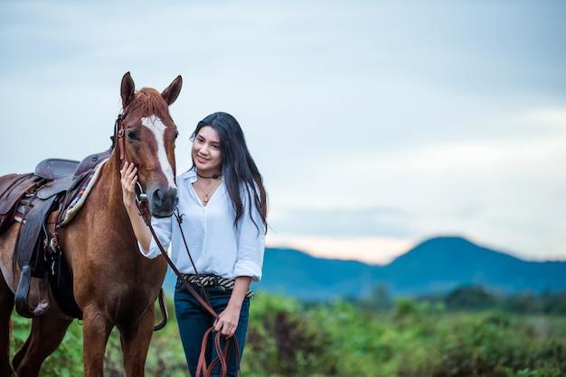 Cowgirl andando em uma montanha com um céu amarelo Foto Premium