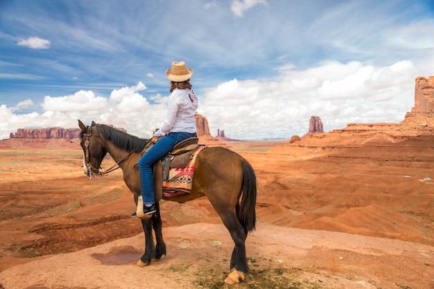 Cowgirl, montando, cavalo, em, monumento, vale, navajo, tribal, parque, eua Foto Premium