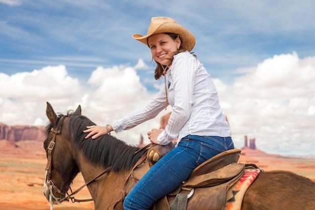 Cowgirl usando chapéu de palha, andar a cavalo em monument valley Foto Premium