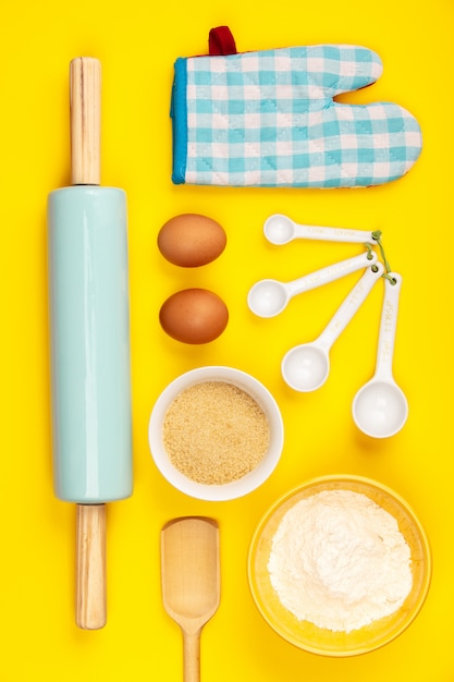 Cozer ou cozinhar ingredientes sobre fundo amarelo, plana leigos Foto Premium
