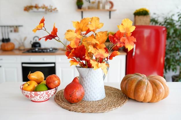 Cozinha de outono com legumes, abóbora e folhas amarelas no vaso na mesa branca. Foto Premium