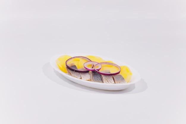 Cozinha russa na forma de batatas com endro e arenque em um prato branco close-up Foto Premium