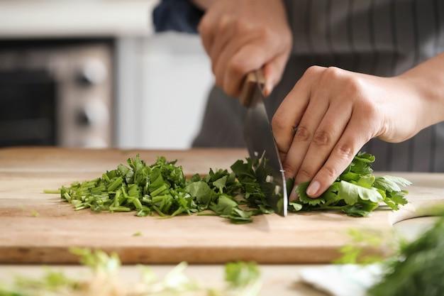 Cozinhando. chef está cortando verduras na cozinha Foto gratuita