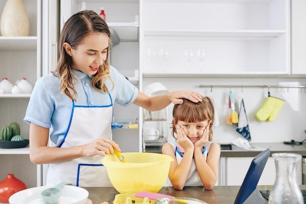 Cozinhando mãe acariciando a cabeça da filha esperando o bolo ser feito Foto Premium