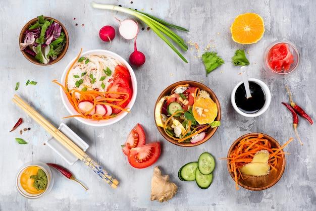 Cozinhando saladas vegetais sortidos e prato asiático no fundo de pedra, Foto Premium