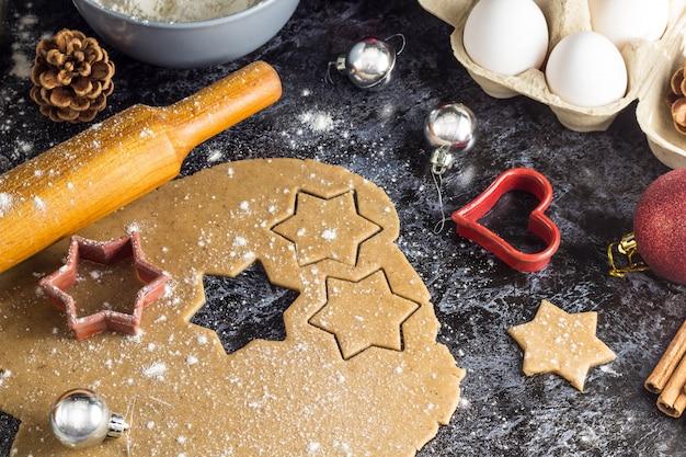 Cozinhar biscoitos de gengibre de natal com ingredientes e decoração em um fundo escuro Foto Premium