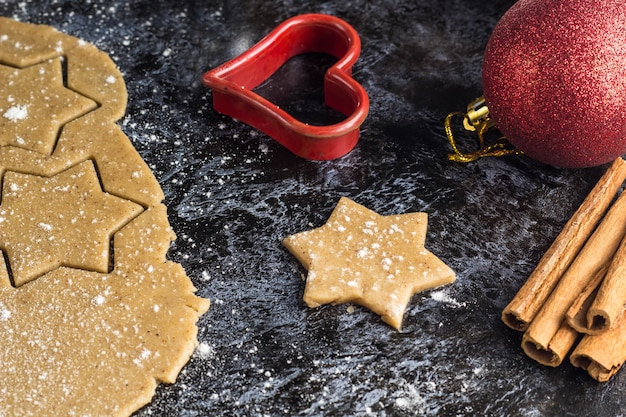 Cozinhar biscoitos de gengibre de natal com ingredientes e decoração no escuro Foto Premium