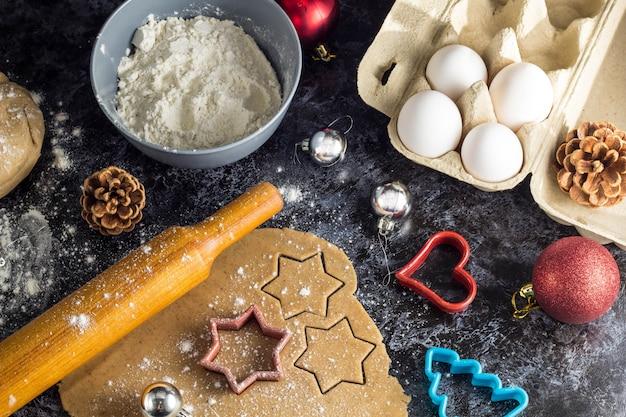 Cozinhar biscoitos de gengibre de natal com ingredientes e decoração Foto Premium