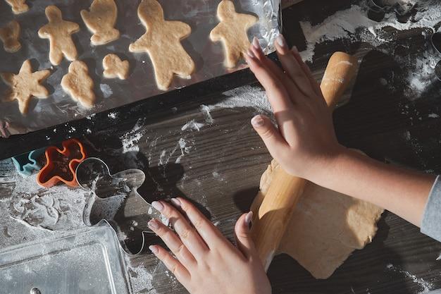 Cozinhar biscoitos de natal na mesa de madeira marrom escura. família fazendo homem-biscoito, cortando biscoitos de massa de pão de gengibre, vista de cima. Foto Premium