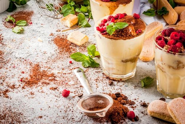 Cozinhar comida italiana sobremesa tiramisu com todos os ingredientes necessários cacau café mascarpone queijo menta e framboesas em fundo de pedra cinza. Foto Premium
