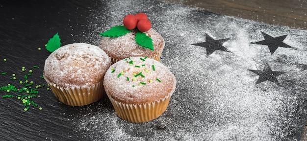 Cozinhar cupcakes de natal e decorá-los com visco Foto Premium