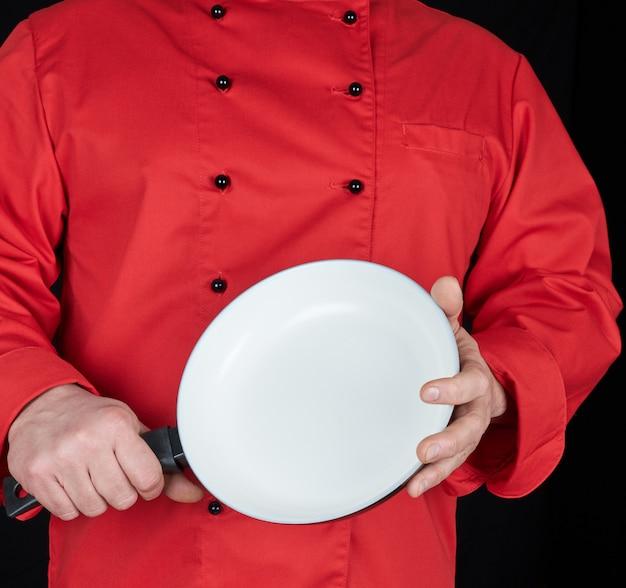 Cozinhar, em, vermelho uniforme, segurando, um, vazio, redondo, branca, frigideira Foto Premium