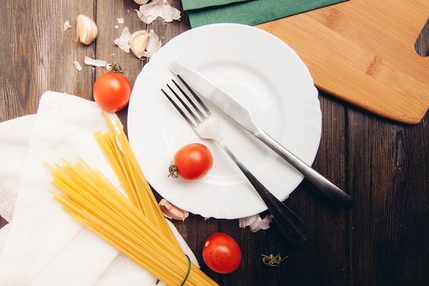Cozinhar macarrão com tomate, mesa de cozinha Foto Premium