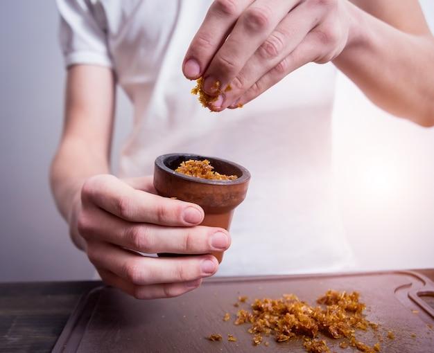 Cozinhar narguilé no bar. corte o tabaco em uma tigela. restaurante, bar de narguilé, café para fumantes. Foto Premium