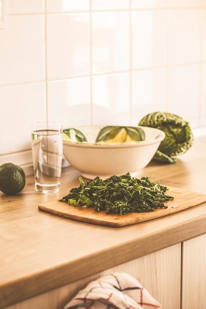 Cozinhar salada verde de couve e abacate na cozinha Foto Premium