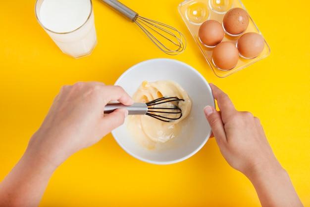 Cozinhar sobremesa ou café da manhã. mãos que misturam ovos crus na bacia. Foto Premium