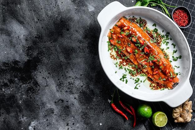 Cozinhar teriyaki de filé de truta do mar. fundo preto Foto Premium