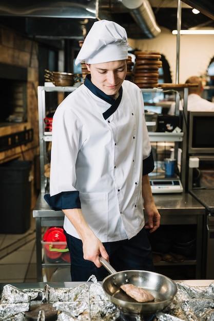 Cozinhe a carne fritando na panela no fogão Foto gratuita