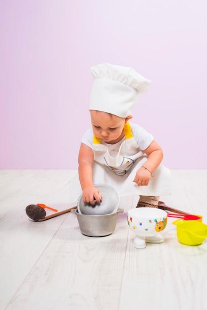 Cozinhe a criança sentada com utensílios de cozinha no chão Foto gratuita