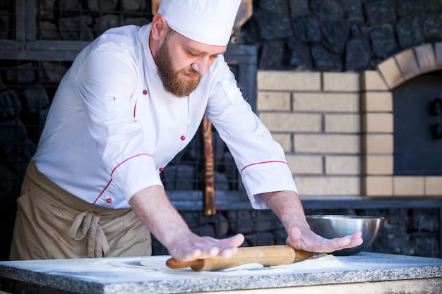 Cozinhe a preparar a pizza em um restaurante. Foto Premium