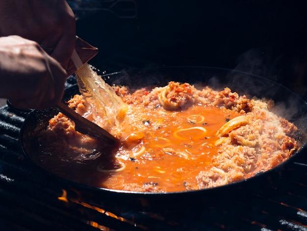 Cozinhe adicionando molho ao arroz com anéis de lula e legumes na frigideira Foto gratuita