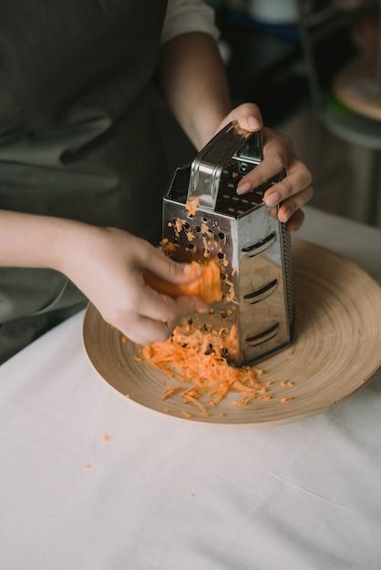Cozinhe as cenouras esfregadas em um ralador em uma tigela. mulher rala cenouras em um ralador. fora de foco, turva Foto Premium