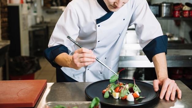 Cozinhe colocando espinafre no prato grande com salada Foto gratuita