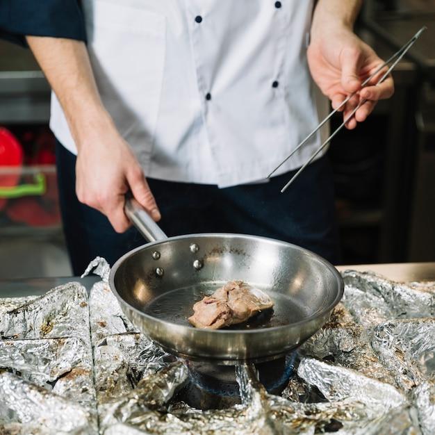 Cozinhe em branco fritar a carne na panela no fogão Foto gratuita