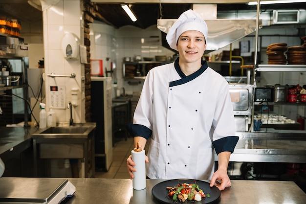 Cozinhe em pé com molho de garrafa e salada Foto gratuita