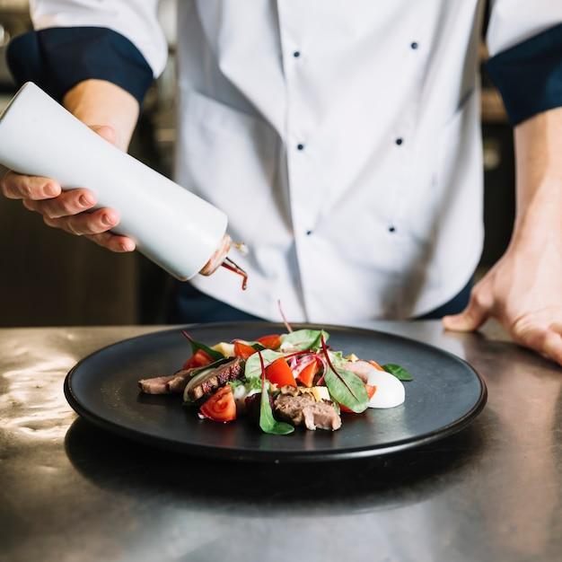 Cozinhe o molho derramando no prato com salada Foto gratuita