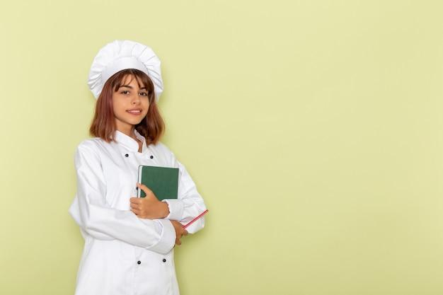 Cozinheira de frente para a cozinheira em um terno branco segurando um caderno verde na superfície verde Foto gratuita