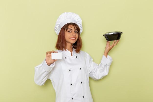 Cozinheira de frente para a cozinheira em um terno branco segurando um cartão branco e uma tigela na superfície verde Foto gratuita