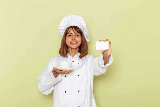 Cozinheira de frente para a cozinheira em um terno branco segurando uma xícara de chá e um cartão na superfície verde Foto gratuita
