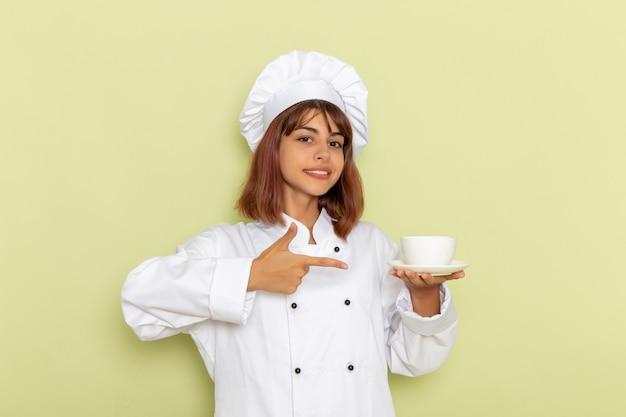 Cozinheira de frente para a cozinheira em um terno branco segurando uma xícara de chá na superfície verde Foto gratuita