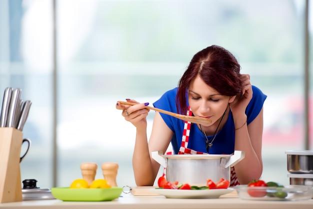 Cozinheira feminina preparando sopa na cozinha bem iluminada Foto Premium