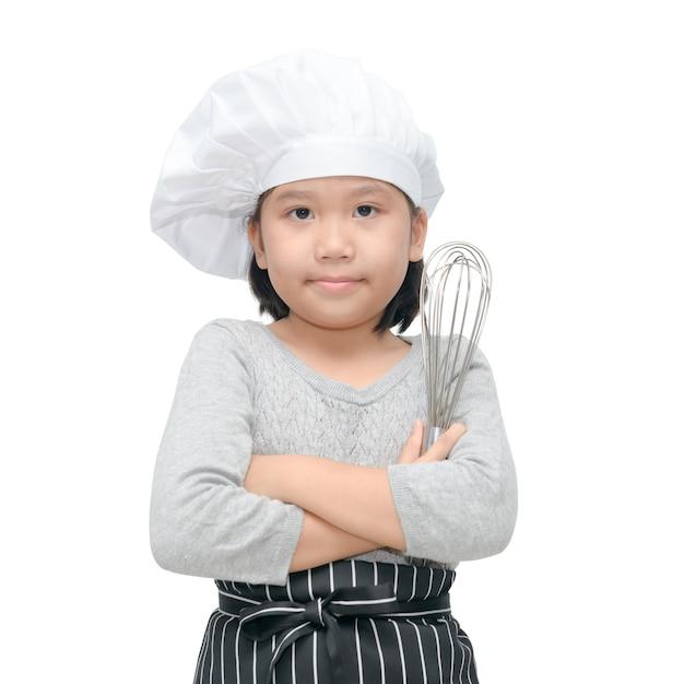 Cozinheiro chefe asiático feliz da menina que guarda utensílios de cozimento e sorriso isolado no fundo branco, imagem quadrada. Foto Premium