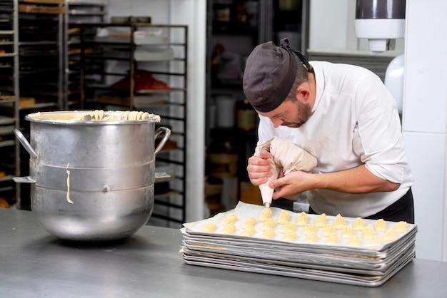 Cozinheiro chefe da pastelaria com o creme de espremedura do saco dos confeitos na loja de pastelaria. Foto Premium