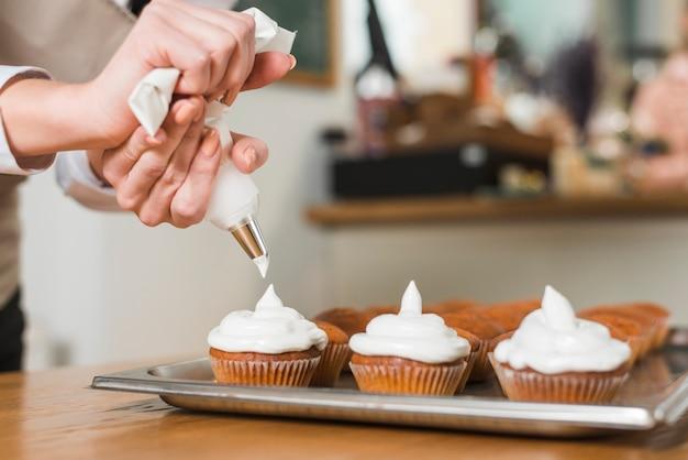 Cozinheiro chefe de pastelaria que decora queques deliciosos com creme Foto gratuita