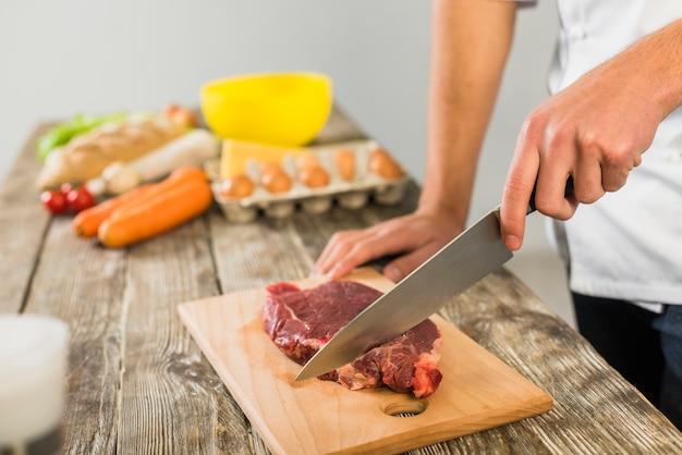 Cozinheiro chefe, em, cozinha, corte, carne Foto gratuita