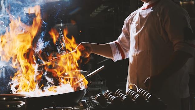 Cozinheiro chefe frite no wok Foto Premium