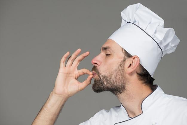 Cozinheiro chefe masculino no uniforme branco que faz o sinal saboroso contra o fundo cinzento Foto gratuita