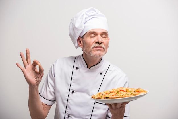 Cozinheiro chefe masculino sênior no uniforme que gesticula o sinal aprovado. Foto Premium