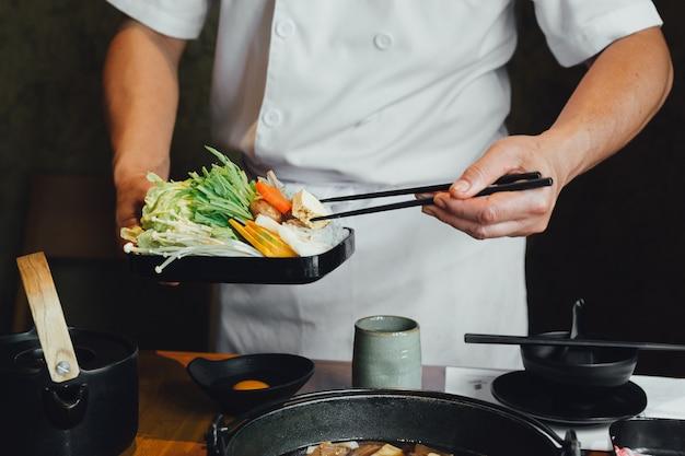Cozinheiro chefe que comprime vegetais no potenciômetro quente por chopsticks antes de derramar a sopa da soja. Foto Premium