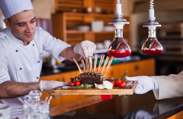 Cozinheiro chefe que cozinha o marisco em um restaurante. Foto Premium