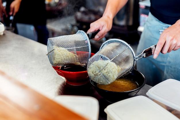 Cozinheiro chefe que ferve o macarronete de ramen na sopa para fazer o miso e os ramen do shoyu. Foto Premium